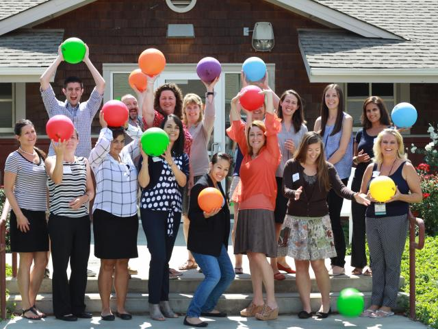 group of smiling people holding colorful balloons