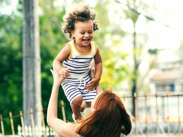 woman playfully throwing her young son in the air