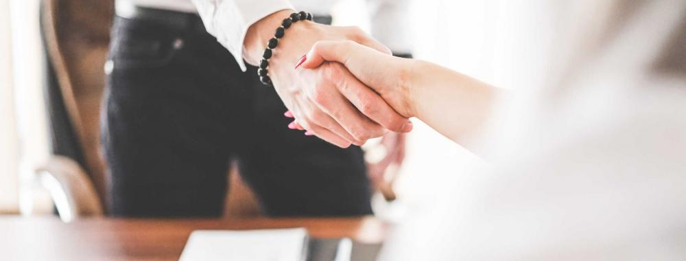 man and woman shaking hands over a desk