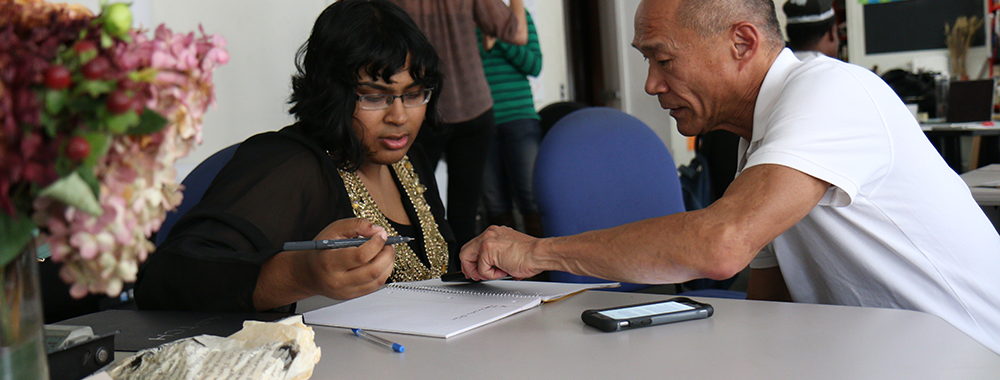 man helping a woman complete a form